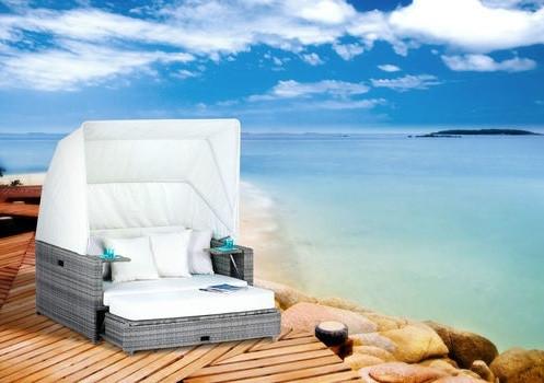 Die Beach Lounge in der Geflechtsfarbe Ash mit creme weißen Kissen.